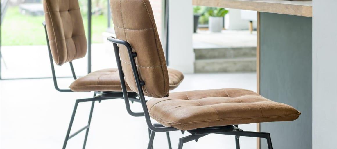 La chaise à surpiqûres se fait aussi chaise de bar avec le modèle H&H Julien. Il arbore un dossier et une assise en cuir anthracite avec un capitonnage très marqué ainsi qu'une structure en métal d'une grande élégance.