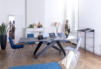"""Dankzij de vormgeving van het frame past de Artella <a href=""""/xn/stoelen/eetkamerstoelen/"""">eetkamerstoel</a> met het vierkante swing onderstel uitstekend in vrijwel iedere eetkamer. De lichtgrijze stof Forli combineert perfect met het RVS-onderstel. Een zeer fraai vormgegeven en uiterst comfortabele eetkamerstoel."""
