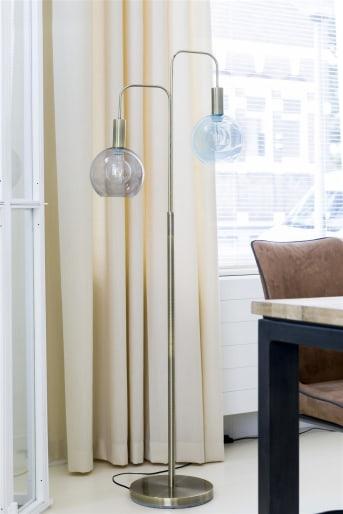 Le lampadaire moderne Gaby signé COCO Maison représente la version moderne d'une lanterne à l'ancienne. Les boules de verre affichent une jolie teinte bleue et gris pastel, tandis que ses détails laiton lui confèrent un look moderne et tendance. À combiner avec la lampe d'appoint et la suspension assorties.