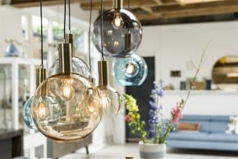 Vous cherchez une suspension moderne au design original? Le modèle Gaby de la collection COCO Maison vous plaira sûrement. Cette suspension comprend 7 ampoules en verre de différentes couleurs et dimensions, ornées de détails laiton. Elle constituera une décoration de choix au-dessus d'une table à manger. Associez ce modèle au lampadaire et à la lampe d'appoint assortis.