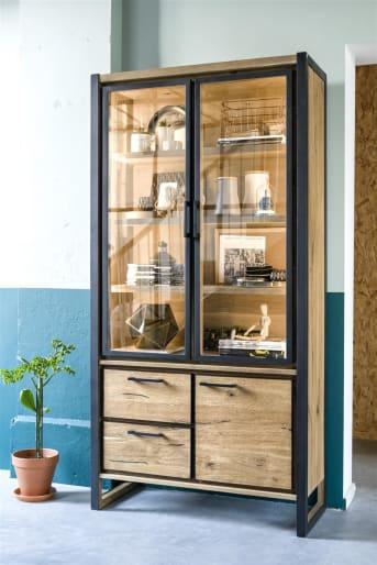 """Ben jij op zoek naar een kast voor het opbergen van al je spullen? Deze prachtige Metalo <a href=""""/hh/kasten/vitrinekasten/"""">vitrinekast</a> uit de collectie van Henders & Hazel heeft een stoer design dankzij de combinatie van eikenhout fineer en metaal. Heel gaaf is hoe het metaal doorloopt van de poten in de rest van de kast. Achter de glazen vitrinedeuren zit geïntegreerde ledverlichting. Dit zorgt voor een mooie belichting van de spullen die je in de kast uitstalt. De Metalo kast is voorzien van 2 laden en een deur. Deze zijn erg handig om spullen uit het zicht in op te bergen. Al je mooie spullen zoals mooie set designvazen of een goede wijncollectie kun je achter de glazen deuren plaatsen voor een leuke sfeer in jouw woonkamer."""