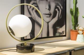 Tafellamp LEAH van COCO maison is een elegante tafellamp die ook mooi als bureaulamp te gebruiken is. Dankzij het witte melkglas geeft LEAH een fijn, diffuus licht af, ook al bevat het item maar één lamp. LEAH heeft een goudkleurige cirkel rondom de witte bollamp, en staat op een zwarte marmer voet. LEAH wordt geleverd exclusief lichtbron.