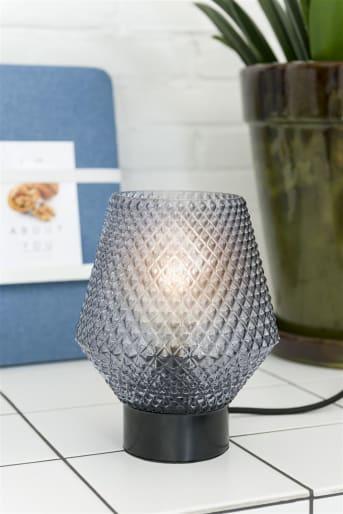 Tafellamp JOYCE van COCO maison doet wat retro aan door zijn ontwerp, en voldoet daarmee helemaal aan de laatste trends. JOYCE is gemaakt van smoked glas, wat ook mede door het reliëf in het glas een mooie sfeer geeft. De tafellamp wordt verkocht exclusief lichtbron, die apart verkrijgbaar is.