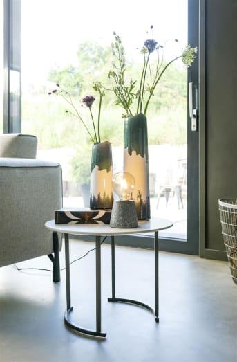 Terrazo is weer terug van weggeweest, en jij kunt nu een trend zetten met deze prachtige tafellamp TERRAZZA van COCO maison! TERRAZZA zorgt voor het vakantiegevoel in huis. De lamp is voorzien van een zwart snoer met lichtknop en er kan een normale E27 lamp in die apart verkrijgbaar is. Deze tafellamp is verkrijgbaar in groen en grijs.