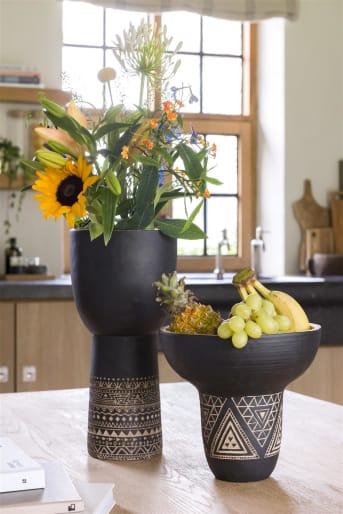 Een mooi vormgegeven pot met een etnische en Afrikaanse uitstraling, dat is pot KENNY medium van COCO maison. KENNY is zwart met bamboe houtkleur aan de binnenzijde en heeft een snijwerk motief aan de buitenzijde. Pot KENNY is leuk om als bloempot en vaas te gebruiken, dit door zijn smalle onderkant en brede bovenkant.