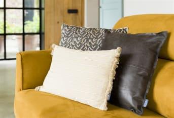 Kussen GLENDALE van COCO maison is een langwerpig model kussen, verkrijgbaar in 2 kleuren: groen/beige en paars/roze. Dit kussen is afgewerkt met een gouden draadje dat in de stof van het kussen is verwerkt.