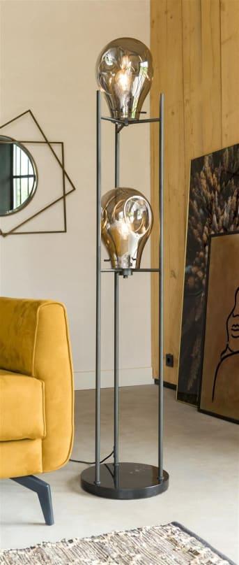 """Le lampadaire CHARLIE signé COCO maison est doté de deux grandes lampes en verre, """"suspendues"""" à une structure noire. CHARLIE repose sur un pied noir, rond et mesure 160 cm de haut. Ce lampadaire trouve aussi bien sa place dans un intérieur industriel que dans un intérieur scandinave et moderne. Il est possible de régler l'intensité de la lumière."""