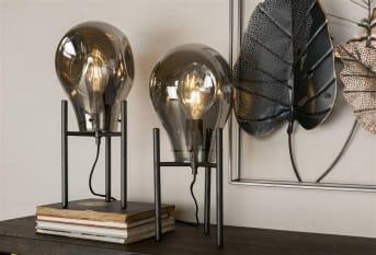 Tafellamp CHARLIE van COCO maison komt uit onze mooie CHARLIE serie waarvan COCO maison ook een hang- en vloerlamp in de collectie heeft. Deze tafellamp bestaat uit 1 grote glazen lamp die op een mooie, zwart metalen voet staat. Tafellamp CHARLIE heeft een hoogte van 49 cm. De lamp bevat een aan/uit schakelaar.