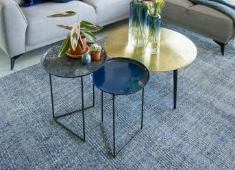 Een set bijzettafels is altijd handig om in huis te hebben. Met deze set bijzettafels NASHVILLE van COCO maison kun je alle kanten op. De ene tafel heeft een glanzend donkerblauw tafelblad en de ander heeft een blauw blad met glasscherven.